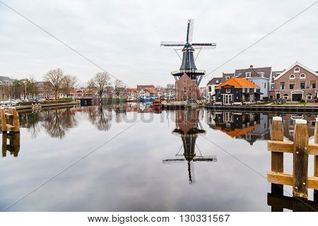 Haarlem, Netherlands - April 2, 2016: Picturesque morning landscape with the windmill and traditional houses Haarlem, Holland