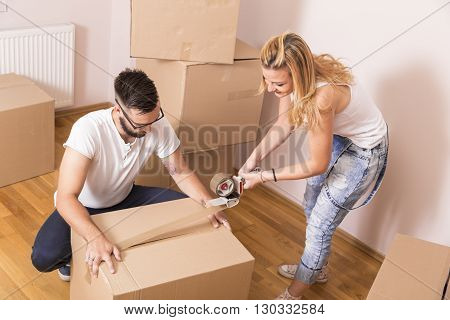 Young girl moving in a new apartment with her boyfriendstanding surrounded with cardboard boxes packing and taping boxes while the boyfrined carries boxes away