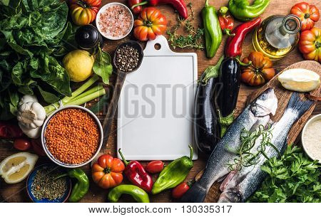 Ingredients for cooking healthy dinner. Raw uncooked seabass fish with vegetables, grains, herbs and spices over rustic wooden background, white ceramic board in center with copy space. Top view