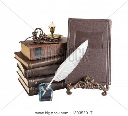 Old books burning candle in candlestick feather pen in inkpot bookrest and bunch of keys isolated on white background