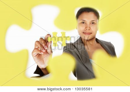 Businesswoman Holding The Last Piece Of Puzzle