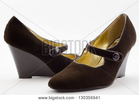 Pair of female brown velvet wedge heel shoes isolated on white