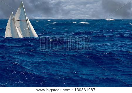 sail ship in big ocean tempest on waves down