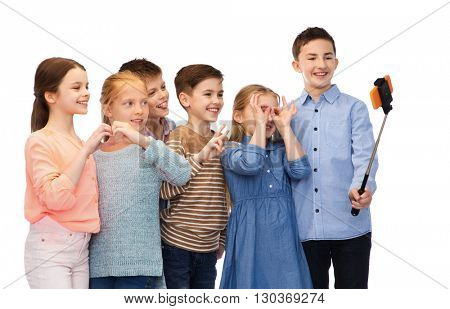 childhood, friendship, technology and people concept - happy children talking picture by smartphone on selfie stick
