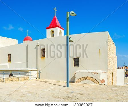 The white walls and red roof of the St John's Church located on the coast of old Akko Israel.