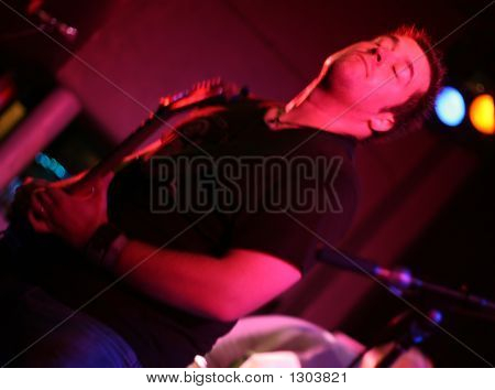 Band Member Playing Guitar And Rocking Out (Slight Motion Blur)