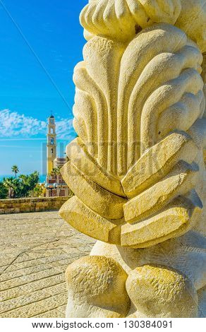 The bell tower of the St peter's church is seen behind the stone sculpture in Abraham Shechterman garden of Jaffa Tel Aviv Israel.