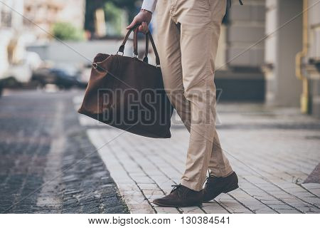 Perfect match. Close-up of man holding leather bag while walking outdoors