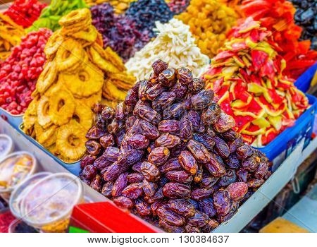 The tasty dried dates pineapple and watermelon slices different raisins in Carmel market of Tel Aviv Israel.