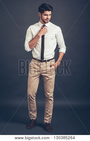 Thoughtful handsome. Full length of confident young handsome man adjusting his tie and looking away while standing against grey background