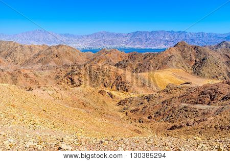 The blue waters of Aqaba Gulf behind the colored Eilat mountains Israel.