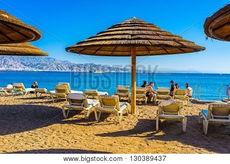 EILAT ISRAEL - FEBRUARY 23 2016: The beache of Eilat are very comfortable they are equipped by big beach umbrellas and soft beach chaise lounge on February 23 in Eilat.