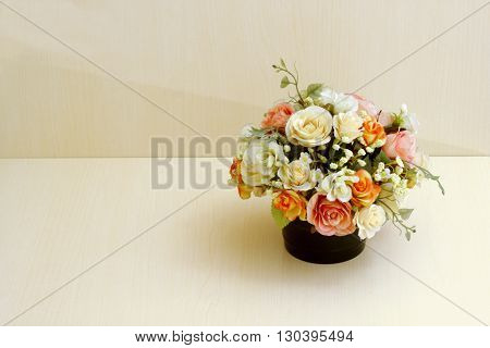Artificial flowers in flowerpot on wooded background.