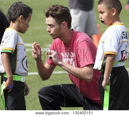 FLAGSTAFF, ARIZONA, MAY 14. Foxglenn Park on May 14, 2016, in Flagstaff, Arizona. A young man coaches a youth flag football team at Foxglenn Park in Flagstaff Arizona.