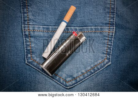 Pack of cigarettes and lighter in pocket of jeans. Closeup
