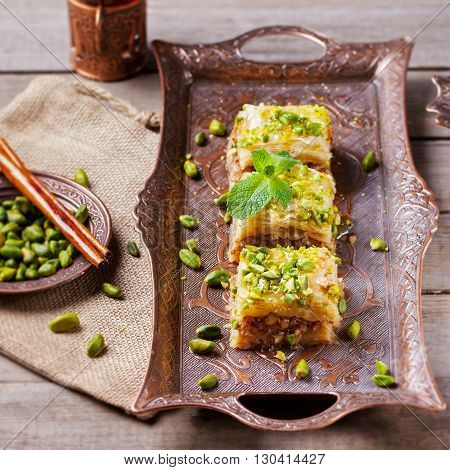 Turkish pistachio and phyllo pastry dessert, baklava on a authentic cooper tray with a plate of pistachios and stick of cinnamon