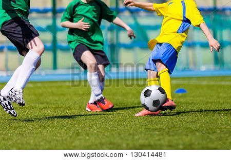 young boys playing football soccer game. Running players in green and yellow uniforms