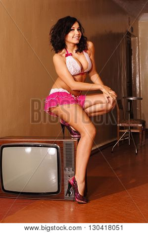 Sensual lady posing in lace lingerie sit on tv