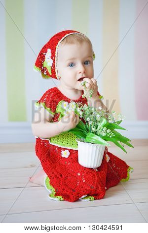 Little girl sitting on floor dressed in red reding hood costume and holding pot with flowers in her hands