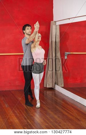 Full Length Of Trainer Assisting Ballet Dancer