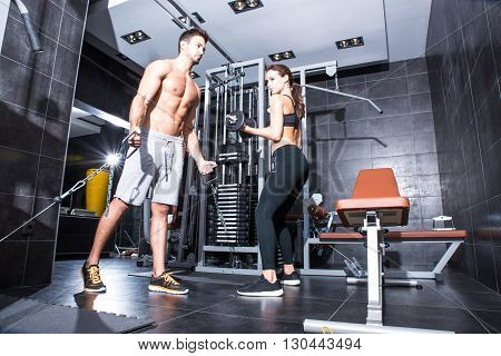 A young couple training together in the Gym.