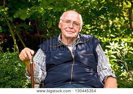Elderly Man Sitting In The Garden