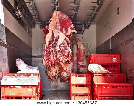 Raw beef, butchery transport. Raw meat hanging on meat hooks in a truck.