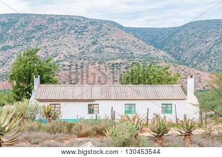 A farm worker duet house with aloes in front in the Baviaanskloof (baboon valley).