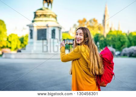 Young female tourist with back pack photographing with smart phone Austrian national hero monument on Hendel square.