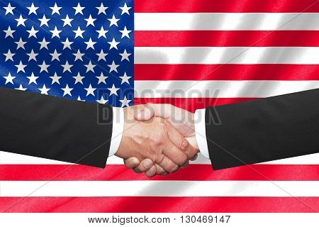 two businessmen shakehand over american national flag