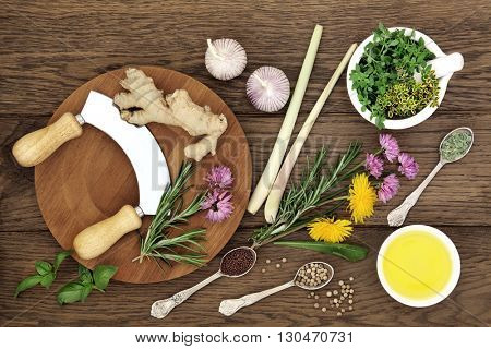 Herb and spice selection with chopper and board, mortar with pestle and olive oil on old oak background.