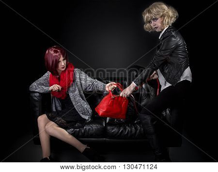 Two jealous fashionable women fighting over red hand bag on a black couch