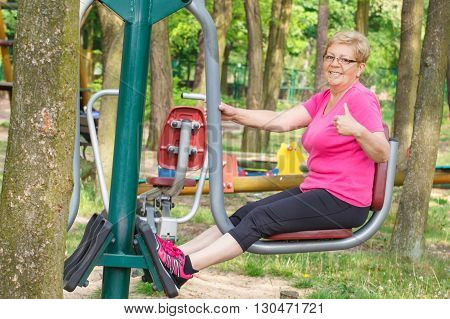 Elderly senior woman in sports wear exercising lower body on outdoor gym in sunny park trainer machine healthy sporty lifestyles and slimming in old age