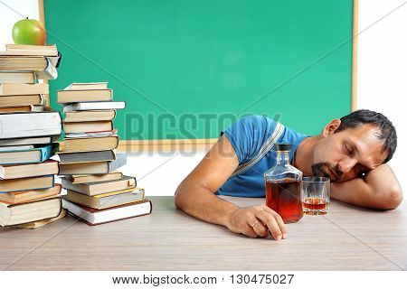 Drunk teacher fall asleep at classroom. Photo of adult man addicted to alcohol at the workplace education concept