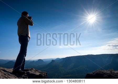 Professional Photographer Takes Photos With Mirror Camera On Cliff Of Rock. Dreamy Misty Landscape,