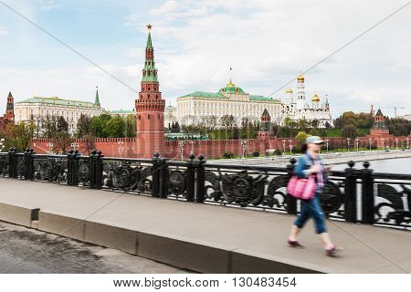 Moscow Russia - May 2 2016: Tourists and citizens on the background of Moscow Kremlin. View from the Big Stone Bridge on the Kremlin fortress Russia. Focus on the Kremlin