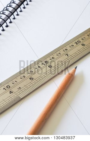 A metal ruler ( featuring both inches and centimetres ) and a lead pencil on a plain piece of white paper.