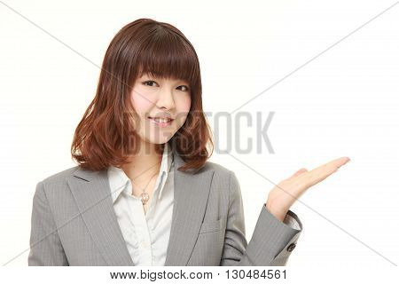 young Japanese businesswoman presenting and showing something
