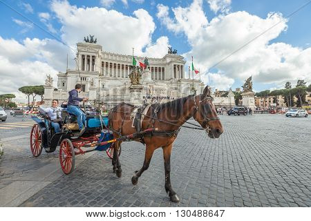 Rome, Italy - May 12, 2016: Typical horse-drawn carriage with tourists in Piazza Venezia with the Vittoriano National Monument or Altar of the Fatherland, one of the Italian and Rome patriotic symbols