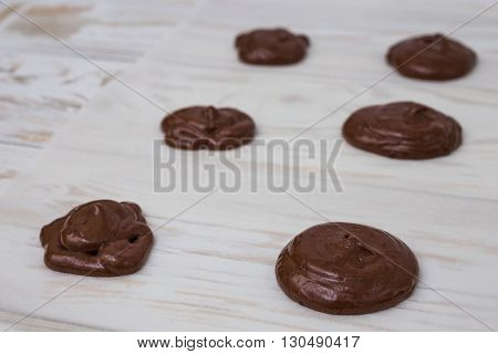 Unbaked chocolate Whoopie pies on white wooden bsckground