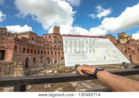 Rome, Italy - May 12, 2016: tourist reading the explanation of archaeological site. Portici Laterali, ruins of the Trajan's Forum, Foro di Traiano, Rome, Lazio, Italy.