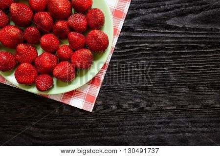 Strawberries in a green plate on a towel