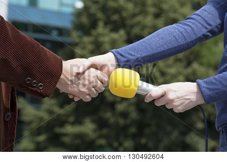 Man and a female reporter shaking hands before media interview