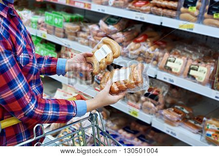 The woman chooses sausages in the store