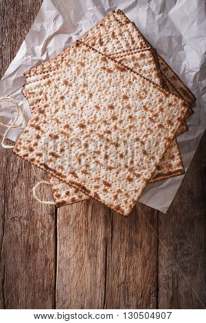Jewish Kosher Matzah Closeup On Paper On A Table. Vertical Top View