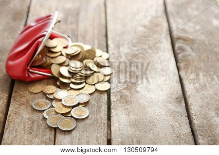 Open red purse and euro coins on wooden table