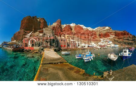 Panoramic view with fishing boats at Old port Amoudi of Oia village at Santorini island in Aegean sea, Greece