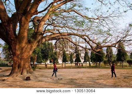 KOLKATA. INDIA - JAN 16. 2013: Two young woman play badminton in the shadow garden near the Victoria Memorial on January 16, 2013 in Kolkata. The Garden of the Memorial was designed on area of 0.26 sq.km