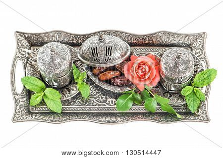 Holidays tea table setting with dates mint leaves and rose flower. Ramadan karim. Oriental hospitality concept