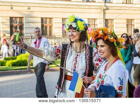 Zaporizhia/Ukraine- May 19, 2016: girls in colorful flower wreaths taking photo on phone using selfy stick on celebration of national Ukrainian embroidered clothes, known as Vyshyvanka  Day